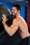Shirtless male athlete lifting tire Stock Image