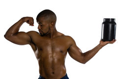 Shirtless male athlete looking at muscles while holding supplement jar Royalty Free Stock Images