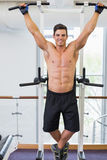 Shirtless male body builder doing pull ups Royalty Free Stock Image