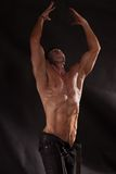 Muscular male torso. Shirtless male bodybuilder on a dark background Stock Images
