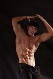 Muscular male torso. Shirtless male bodybuilder on a dark background Royalty Free Stock Photo