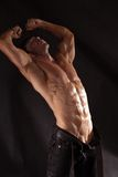 Muscular male torso. Shirtless male bodybuilder on a dark background Royalty Free Stock Photos