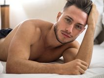Free Shirtless Male Model Lying Alone On His Bed Royalty Free Stock Images - 130493749