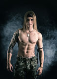 Shirtless male model smiling. Shirtless male model wearing a bandanna and military pants smiling on smoky background Stock Photo