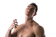 Shirtless male model spraying cologne Royalty Free Stock Photos