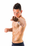 Shirtless male model throwing punch towards camera Royalty Free Stock Image