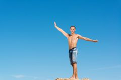 Shirtless man against blue sky. Shirtless man spread his hands against the blue sky Stock Images