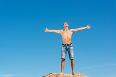 Shirtless man against blue sky. Shirtless man spread his hands against the blue sky Royalty Free Stock Image