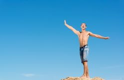 Shirtless man against blue sky. Shirtless man spread his hands against the blue sky Stock Image