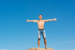 Shirtless man against blue sky. Shirtless man spread his hands against the blue sky Royalty Free Stock Images