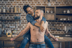 Shirtless man and attractive young woman hugging in kitchen at morning Stock Photo