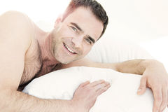 Shirtless man in bed and smiling Stock Photo