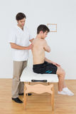 Shirtless man being examined by a physiotherapist in office Stock Images