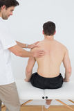 Shirtless man being massaged by a physiotherapist Royalty Free Stock Photography
