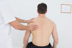 Shirtless man being massaged by a physiotherapist Stock Image