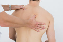 Shirtless man being massaged by a physiotherapist Royalty Free Stock Photo