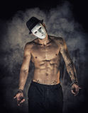 Shirtless man dancer or actor with creepy, scary mask. On tilted head, on dark smoky background Stock Image