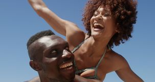 Shirtless man die op de rug rit geven aan vrouw bij strand 4k stock video