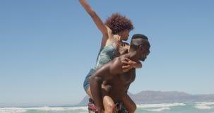 Shirtless man die op de rug rit geven aan vrouw bij strand 4k stock videobeelden