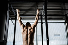 Shirtless man doing pull up. At the crossfit gym Stock Image