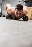 Shirtless man doing push up with dumbbells stock photo