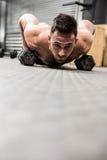 Shirtless man doing push up with dumbbells stock photo