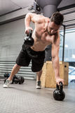 Shirtless man doing push up with kettlebells stock image
