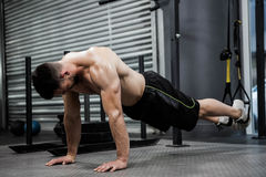 Shirtless man doing push up with the rope. At the crossfit gym Stock Photography