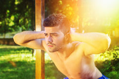 Shirtless man doing squats outdoors on sunny summer day Royalty Free Stock Images