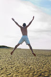 Shirtless Man Doing Star Jump On Beach Stock Photo