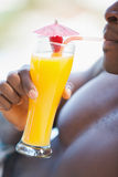 Shirtless man drinking orange cocktail Royalty Free Stock Images