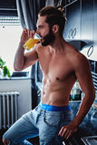 Shirtless man drinking orange juice in the kitchen. Shirtless hipster man drinking orange juice in the kitchen while leaning on the counter Stock Image