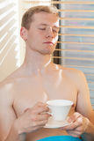 Shirtless man enjoying sunny day sitting near the window Stock Photos