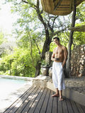 Shirtless Man Enjoying The View On Terrace. Full length of a young shirtless man on terrace enjoying the view Stock Photography
