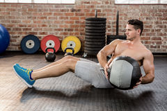 Shirtless man exercising with medicine ball Stock Photography