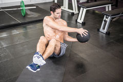 Shirtless man exercising with medicine ball. At the gym stock photo