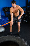 Shirtless man exercising with sledgehammer Royalty Free Stock Photography