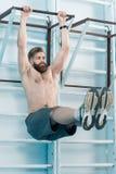 Shirtless man exercising on sport equipment in gym Stock Image