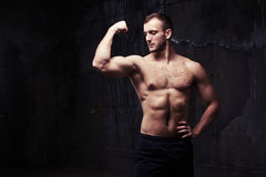 Shirtless man flexing muscles showing great relief of his arms a Royalty Free Stock Photo