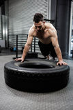 Shirtless man flipping heavy tire Stock Images