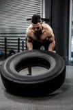 Shirtless man flipping heavy tire Stock Photos