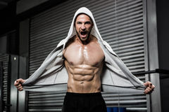 Shirtless man with grey jumper shouting. At the crossfit gym Royalty Free Stock Image