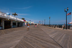 Shirtless Man with Hat Walking on Boardwalk Stock Images