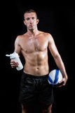 Shirtless man holding bottle and ball Stock Image