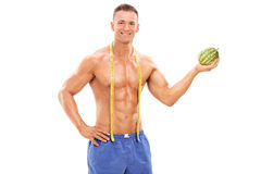 Shirtless man holding a tiny watermelon Royalty Free Stock Photo