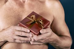 Shirtless man holds a gift box isolated on white. Surprise. Studio shot. Holiday and special occasion. stock images