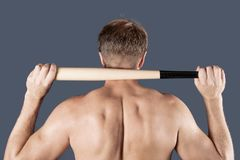 Shirtless man holds on his shoulders a baseball bat over blue background stock photos