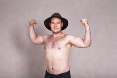 Shirtless man i hatten som poserar och visar hans starka kropp Fotografering för Bildbyråer