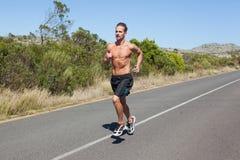 Shirtless man jogging on open road Stock Photo