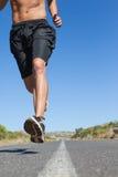 Shirtless man jogging on open road Royalty Free Stock Photo